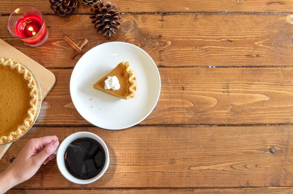 Slice of pumpkin pie with cup of coffee