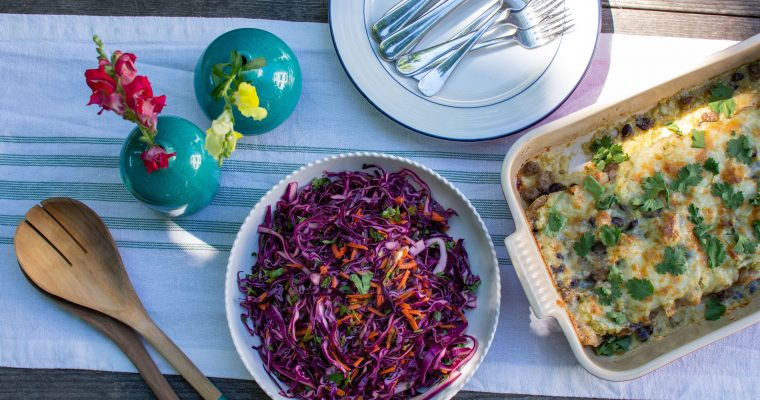 Photo of dinner set on table with beef enchiladas, purple slaw, and turquoise vases of flowers. Boston Area Meal Delivery Service.