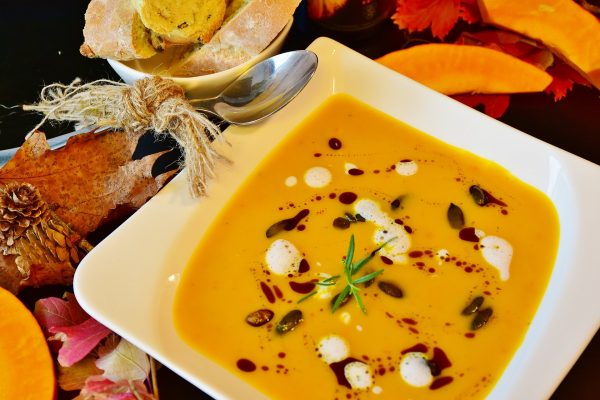 Bowl of butternut squash soup with white and dark red garnishes