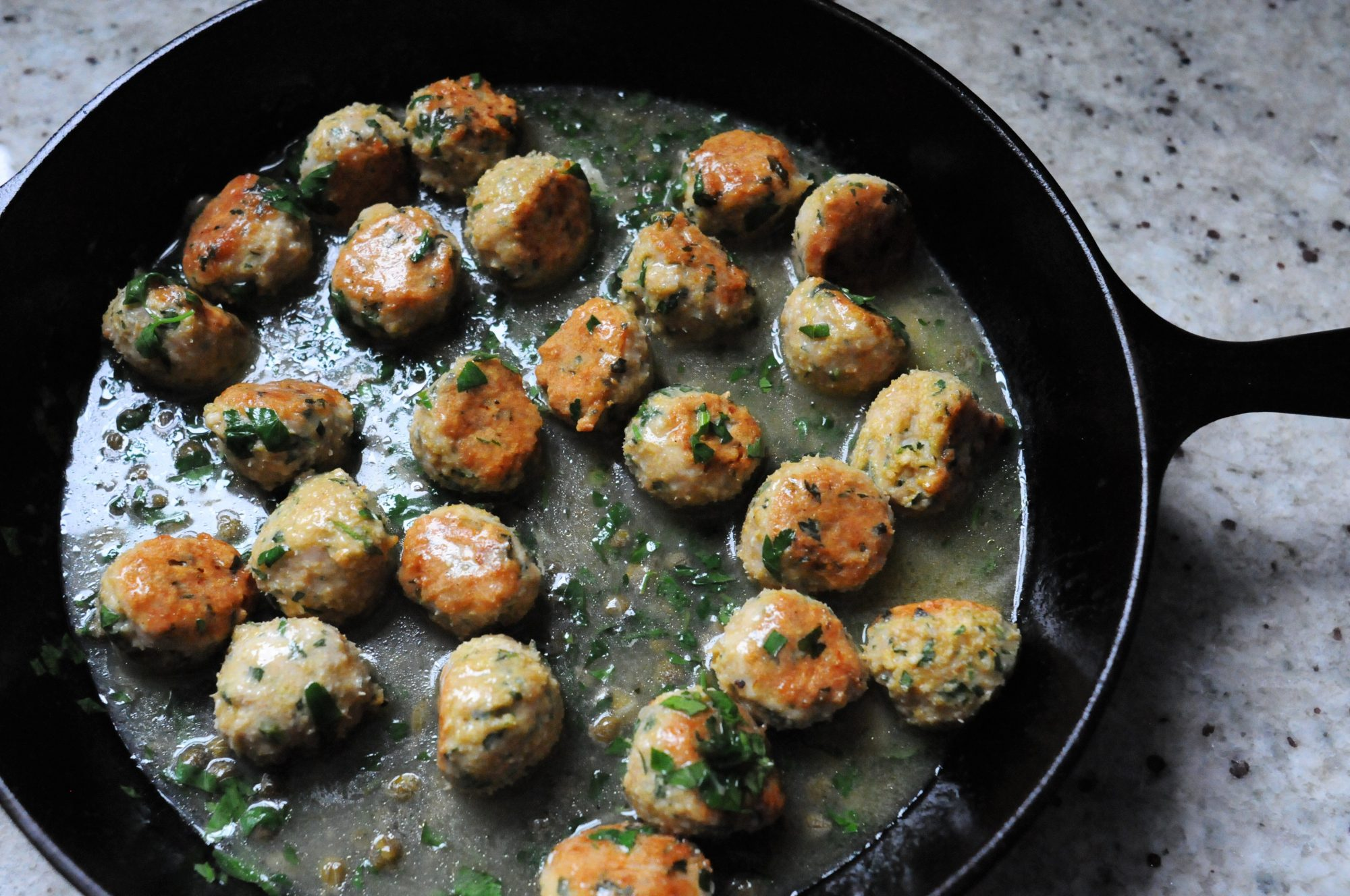 Chicken Picatta Meatballs in black cast iron skillet